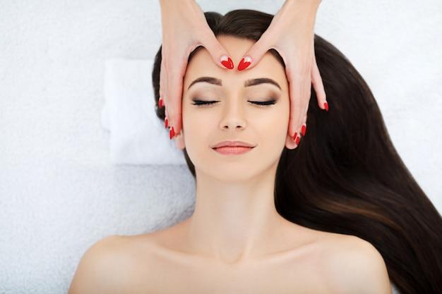 Mooie jonge vrouw krijgt een gezichtsbehandeling bij schoonheidssalon.