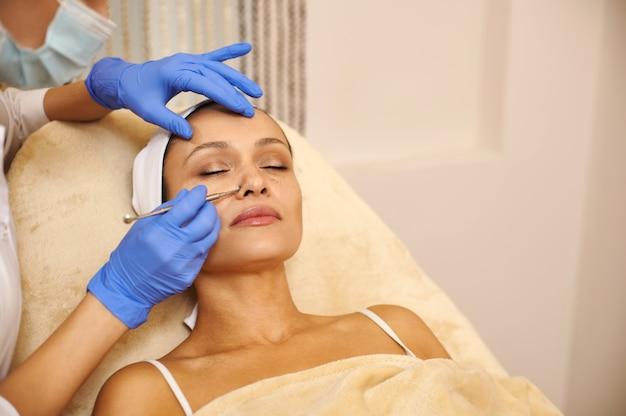 Mooie jonge vrouw krijgt mechanische reiniging van haar gezicht door een schoonheidsspecialiste