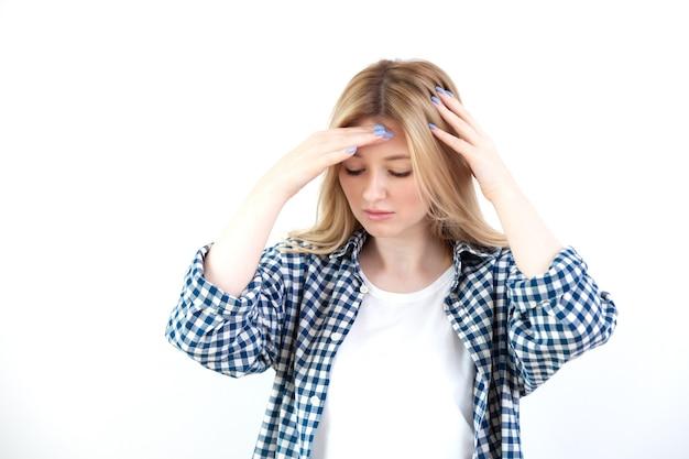 Mooie jonge vrouw legt handen op het hoofd, voelt hoofdpijn