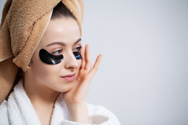 Mooie jonge vrouw legt patches onder de ogen in de badkamer