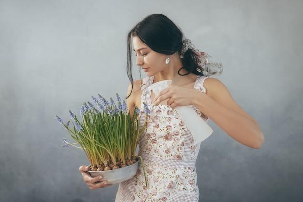 Mooie jonge vrouw lentebloemen in bloempot water geven