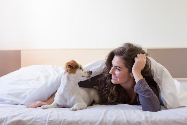 Mooie jonge vrouw liggend op bed onder de witte dekking met haar schattige kleine hond. thuis, binnenshuis en levensstijl