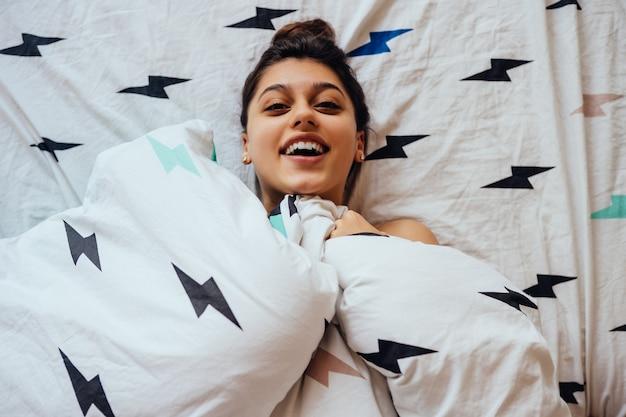 Mooie jonge vrouw ligt in bed, bedekt met een deken