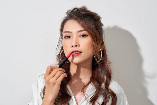 Mooie jonge vrouw lippenstift op de lippen te zetten