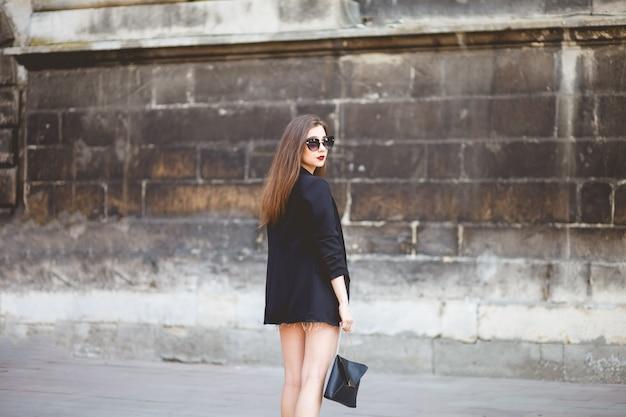 Mooie jonge vrouw loopt door de stad in een stijlvolle outfit