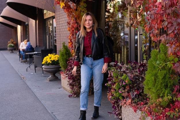 Mooie jonge vrouw lopen langs de straat naast winkels herfst seizoen. gelukkige mensen lopen. vrouw gekleed lederen jas en spijkerbroek buitenshuis. vrije ruimte voor tekst. moderne vrouw.