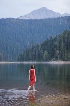 Mooie jonge vrouw lopen op het water van bergmeer