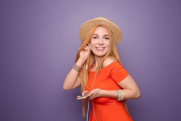 Mooie jonge vrouw luisteren naar muziek op kleur