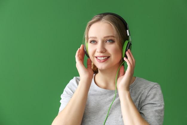 Mooie jonge vrouw luisteren naar muziek tegen groene muur