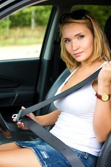 Mooie jonge vrouw maakt een veiligheidsgordel in de auto - buitenshuis