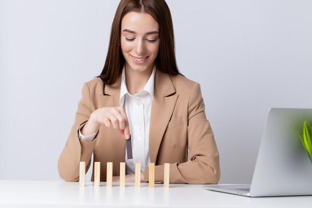 Mooie jonge vrouw maakt houten kubussen op het bureau in het kantoor