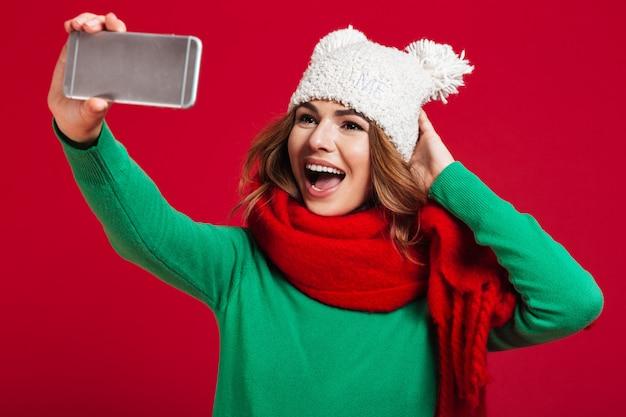 Mooie jonge vrouw maakt selfie telefonisch.