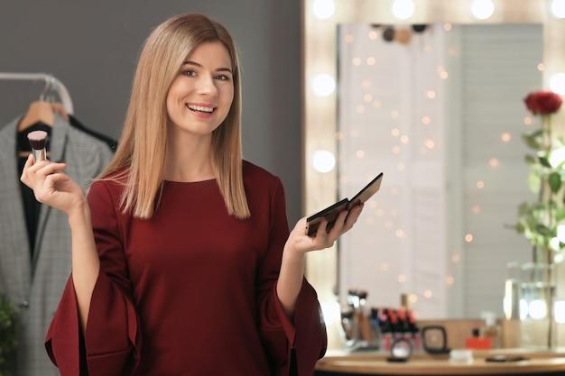 Mooie jonge vrouw make-up in de kamer toe te passen