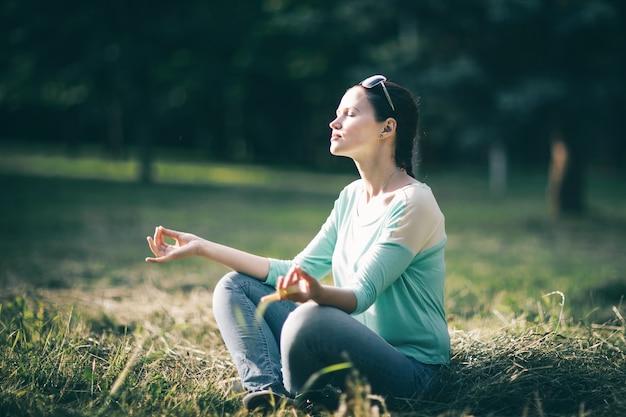 Mooie jonge vrouw mediteren in de lotuspositie zittend op het gazon. foto met kopieerruimte