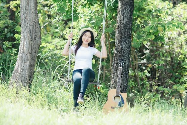 Mooie jonge vrouw met acustic-gitaar bij aard