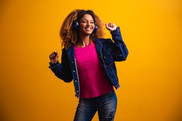 Mooie jonge vrouw met afro haar, luisteren naar muziek met haar koptelefoon en dansen op een gele achtergrond.