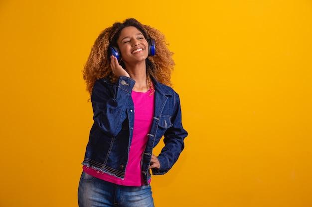 Mooie jonge vrouw met afro haar luisteren naar muziek met haar koptelefoon op gele achtergrond met vrije ruimte voor tekst.