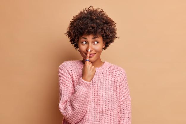 Mooie jonge vrouw met afro haar wijst naar neus met wijsvinger heeft blije uitdrukking dwazen rond en kijkt weg gekleed in gebreide trui geïsoleerd over bruine muur