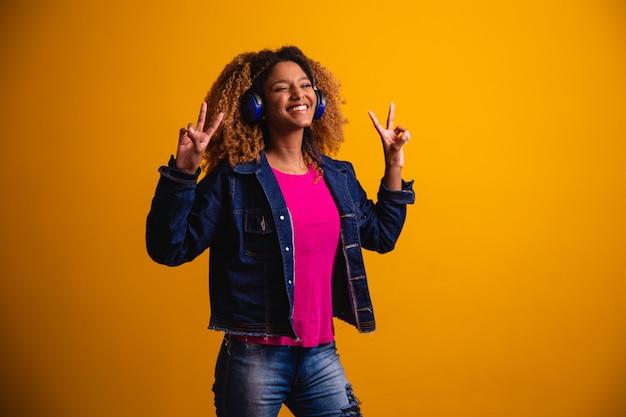 Mooie jonge vrouw met afrohaar met hoofdtelefoons en goede vibe op gele achtergrond