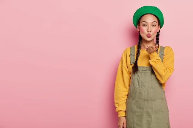 Mooie jonge vrouw met aziatische uitstraling, blaast lucht kus, houdt de lippen rond, draagt make-up, spreekt liefde uit voor iemand, draagt modieuze kleding