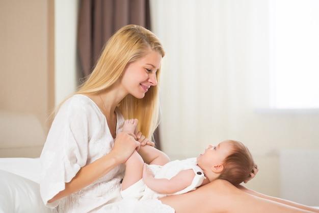 Mooie jonge vrouw met babymeisje in haar armen in de huiskamer 's ochtends