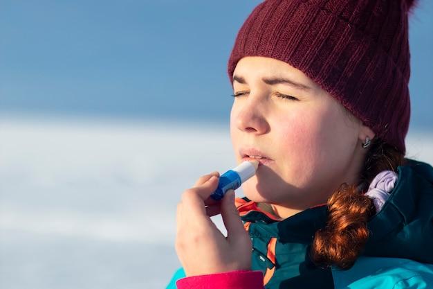 Mooie jonge vrouw met behulp van een hygiënische lippenstift op haar lippen