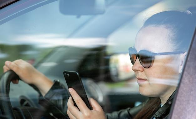 Mooie jonge vrouw met behulp van een slimme telefoon, mobiel tijdens het besturen van een auto, transport concept