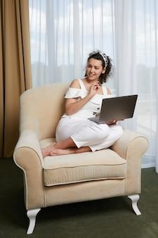 Mooie jonge vrouw met behulp van laptop zittend in leunstoel concept van ontspannen zakelijke dame in hotel