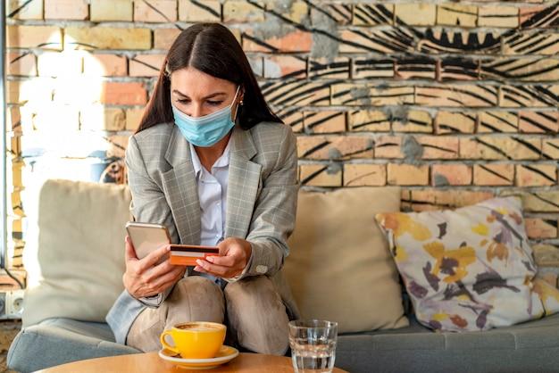 Mooie jonge vrouw met beschermend gezichtsmasker met behulp van mobiele telefoon anc creditcard in het café