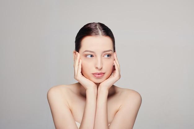 Mooie jonge vrouw met blauwe ogen frisse schone huid die haar gezicht met beide handen raakt.