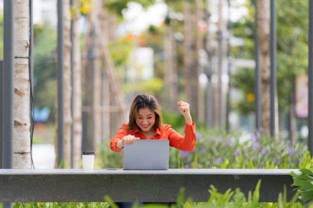Mooie jonge vrouw met blij schreeuwend verbaasd gezicht met behulp van laptop in een stadspark