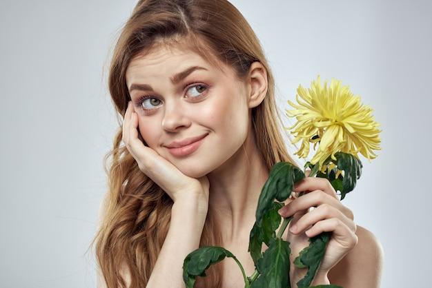 Mooie jonge vrouw met bloem het stellen op een lichte muur, romantisch teder beeld, vrouwenportret