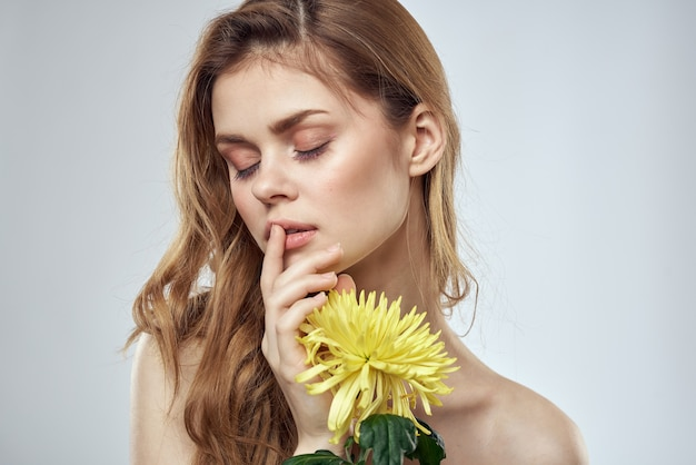 Mooie jonge vrouw met bloem poseren in studio op een lichte achtergrond, romantisch teder beeld, portret van de vrouw