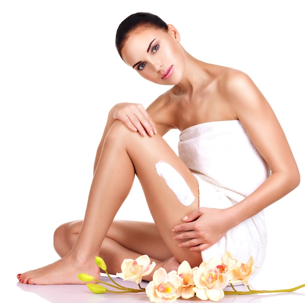 Mooie jonge vrouw met bloemen die de room gebruiken. geïsoleerd op wit