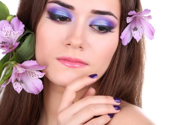 Mooie jonge vrouw met bloemen geïsoleerd op wit