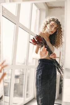 Mooie jonge vrouw met bloemen heeft een fotosessie. meisje met krullend haar draagt jeans.