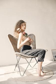 Mooie jonge vrouw met bloemen heeft een fotosessie. meisje met krullend haar zittend op een stoel.