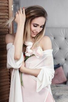 Mooie jonge vrouw met bloemen in haar handen