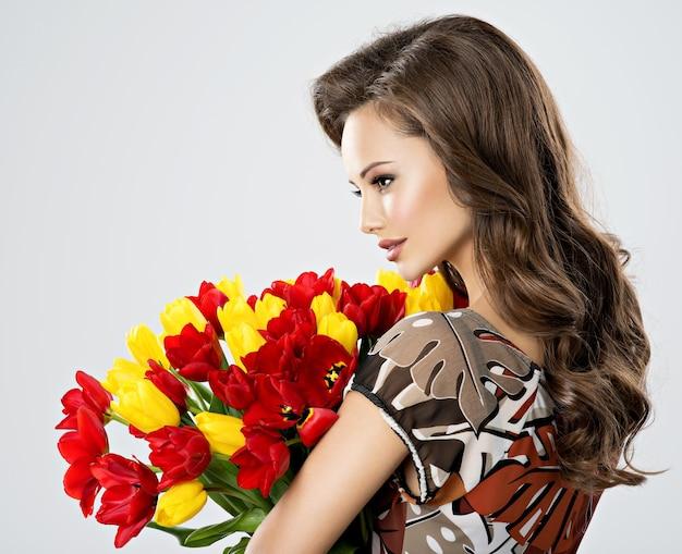 Mooie jonge vrouw met bloemen in handen. mooi meisje houdt de rode tulpen. profiel portret