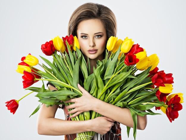 Mooie jonge vrouw met bloemen in handen. mooi meisje houdt de rode tulpen