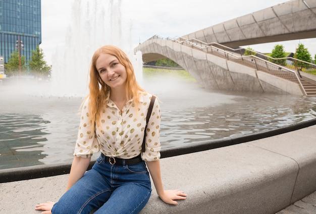 Mooie jonge vrouw met blond haar poseren in de buurt van fontein in de stad