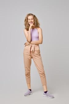 Mooie jonge vrouw met blond slordig haar in mouwloos onderhemd en broek die de kin met een hand steunen