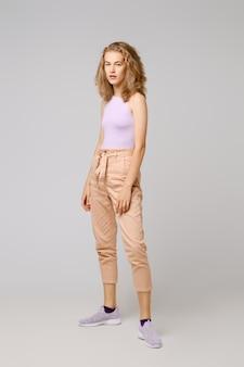 Mooie jonge vrouw met blond slordig haar in mouwloos onderhemd en broeken die over grijs stellen