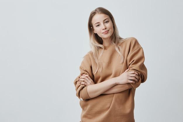 Mooie jonge vrouw met blond steil haar dat zachtjes lacht terwijl ze naar een interessant gesprek luistert, een losse trui met lange mouwen draagt en haar armen over elkaar houdt.