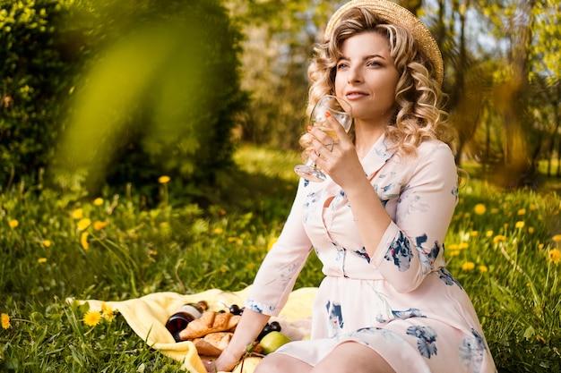 Mooie jonge vrouw met blonde haren in strooien hoed drinkt wijn en zittend op de plaid in de tuin tijdens een zomerpicknick