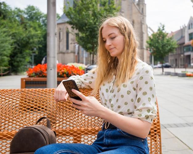 Mooie jonge vrouw met blonde haren messaging op de smartphone in de stad straat. meisje zittend op een bankje en sms typen op de telefoon in de straat op een zonnige dag. actief leven concept
