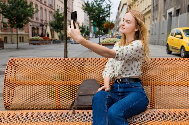 Mooie jonge vrouw met blonde haren selfie te nemen op de straat in de stad. meisje zittend op een bankje in een zonnige dag. actief leven concept