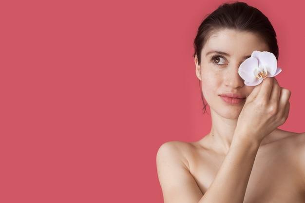 Mooie jonge vrouw met blote schouders bedekt haar oog met een bloem die reclame maakt voor iets op een rode studiomuur