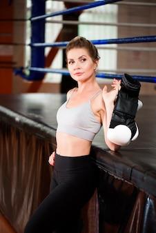 Mooie jonge vrouw met bokshandschoenen poseren en kijken naar de camera.