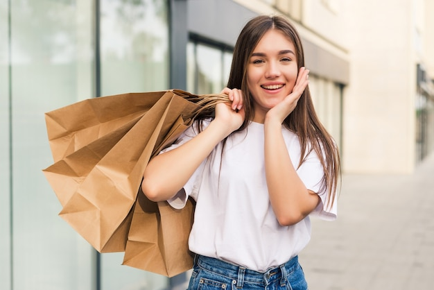 Mooie jonge vrouw met boodschappentassen en lachend buitenshuis